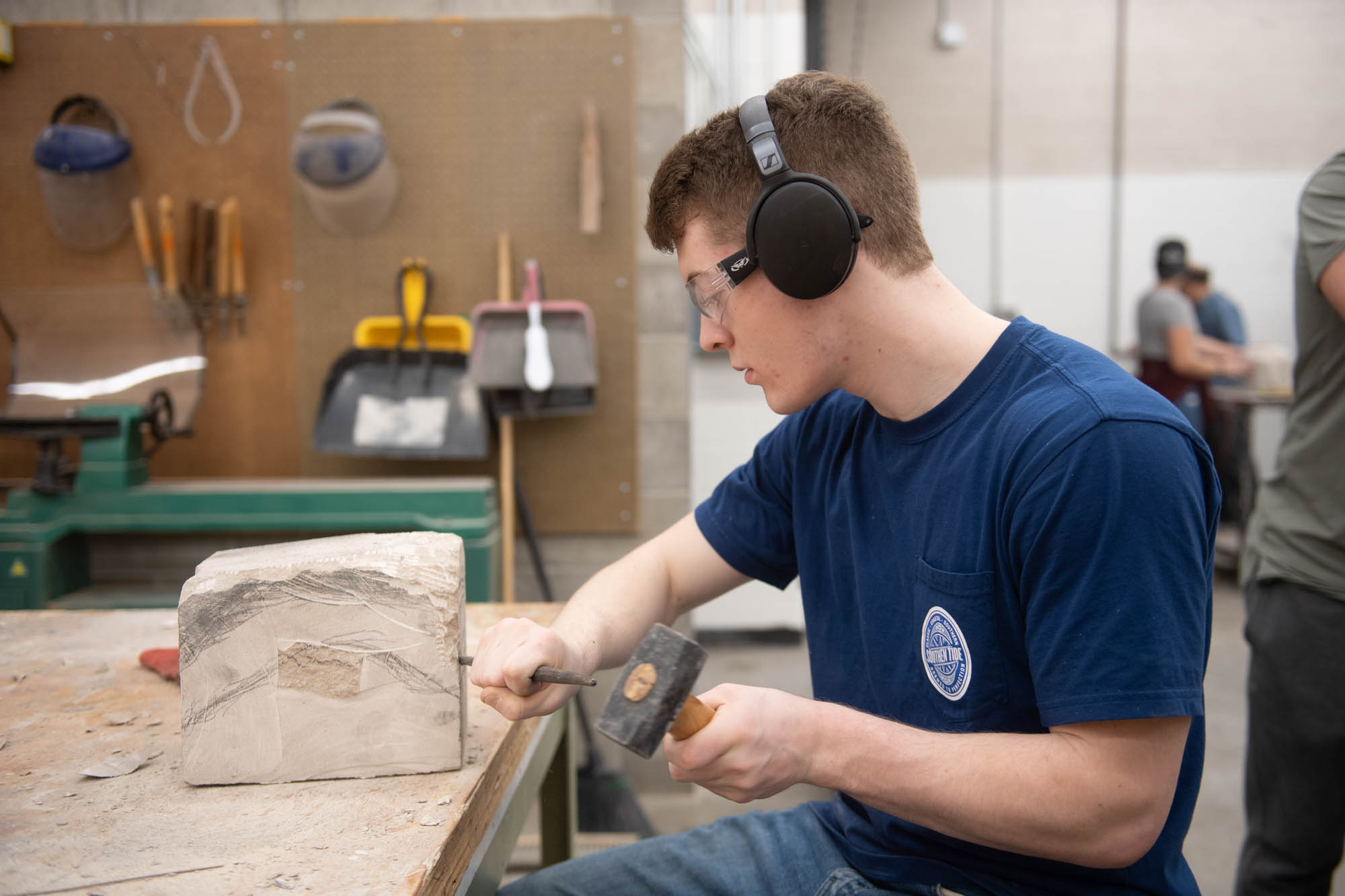 Art student chiseling limestone at Illinois Wesleyan University