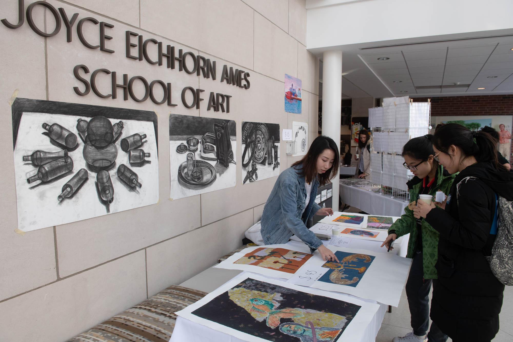 Student artist pointing at art print in front of Joyce Eichhorn Ames School of Art sign
