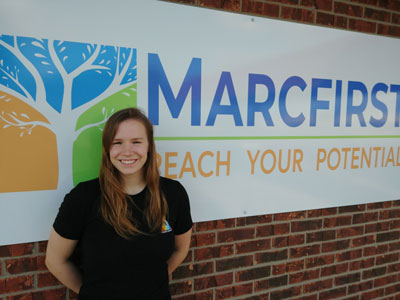 Macey in front of the Marcfirst sign