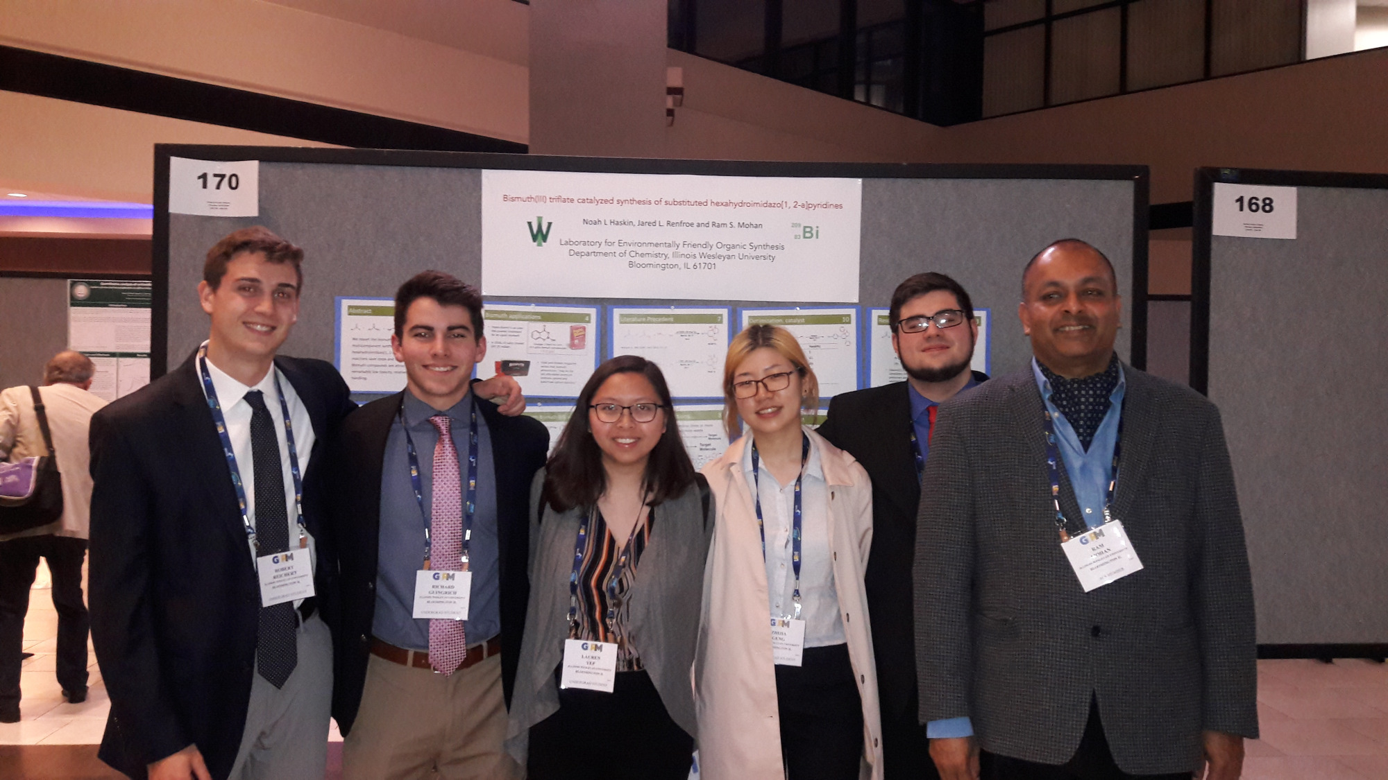 Research Group with Dr. Mohan in front of poster presentation.