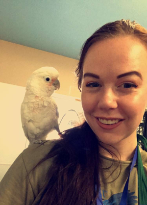 Lindsey Peters with a cockatoo on her shoulder.
