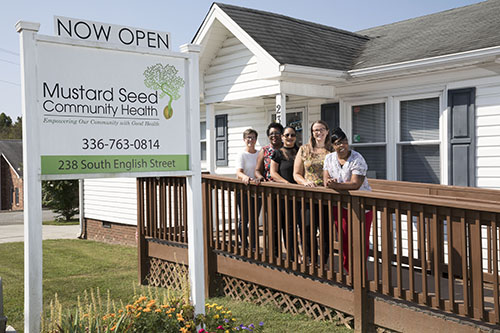 The Mustard Seed Community Health staff poses for a photo outside the clinic's front door.