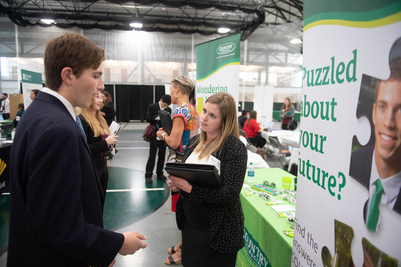 Student talking to COUNTRY Financial recruiter at an IWU Career Fair.
