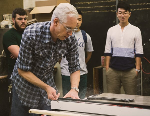 "Visiting Assistant Professor of Design Technology and Entrepreneurship (DTE) Mark Genrich demonstrates a table saw to students in his course ""Beginning 3-D Design."""