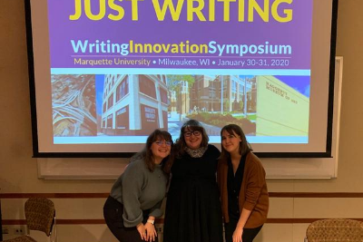 Tutors pose in front of a Marquette Writing Symposium sign